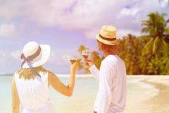 Ευτυχές κρασί κατανάλωσης ζευγών αγάπης στην παραλία στοκ φωτογραφία