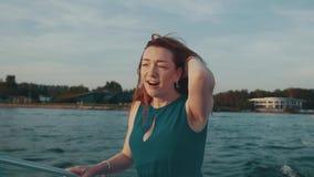 Ευτυχές κόκκινο κορίτσι τρίχας στον τυρκουάζ χορό φορεμάτων στη βάρκα μηχανών Τρίχα κουνημάτων Διασκέδαση φιλμ μικρού μήκους