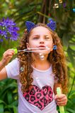 Ευτυχές λίγο σγουρό κορίτσι που παίζει με το σαπούνι βράζει σε μια θερινή φύση, φθορά μπλε αυτιά των εξαρτημάτων τιγρών πέρα από  Στοκ Φωτογραφίες