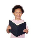 Ευτυχές λατινικό παιδί με μια ανάγνωση βιβλίων Στοκ Φωτογραφία