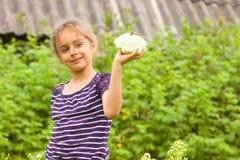 Ευτυχές λατρευτό μικρό κορίτσι που συγκομίζει τις φρέσκες κολοκύνθες σε έναν κήπο και που κρατά τη μικρή φρέσκια κολοκύνθη στο χέ στοκ εικόνες με δικαίωμα ελεύθερης χρήσης