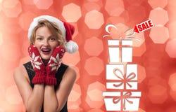 ευτυχές λευκό αγορών πώλησης κοριτσιών Χριστουγέννων ανασκόπησης διακοπές Όμορφη γυναίκα στο καπέλο santa με το δώρο Χριστουγέννω Στοκ Εικόνες