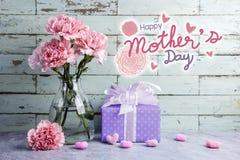 Ευτυχές μήνυμα ημέρας μητέρων στο ξύλινο υπόβαθρο και το ρόδινο γαρίφαλο στοκ εικόνες