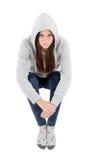 Ευτυχές με κουκούλα κορίτσι με την γκρίζα συνεδρίαση μπλουζών στο πάτωμα Στοκ Εικόνες