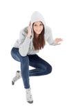 Ευτυχές με κουκούλα κορίτσι με την γκρίζα συνεδρίαση μπλουζών στο πάτωμα Στοκ εικόνα με δικαίωμα ελεύθερης χρήσης