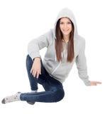 Ευτυχές με κουκούλα κορίτσι με την γκρίζα συνεδρίαση μπλουζών στο πάτωμα Στοκ Φωτογραφίες