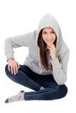 Ευτυχές με κουκούλα κορίτσι με την γκρίζα συνεδρίαση μπλουζών στο πάτωμα Στοκ εικόνες με δικαίωμα ελεύθερης χρήσης