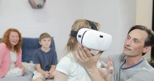 Ευτυχές μικρό κορίτσι εκμετάλλευσης πατέρων που φορά τα γυαλιά εικονικής πραγματικότητας στην κρεβατοκάμαρα, οικογενειακό πρωί μα φιλμ μικρού μήκους