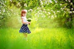 Ευτυχές μικρό κορίτσι με μια ανθοδέσμη των κρίνων της κοιλάδας που έχει Στοκ φωτογραφία με δικαίωμα ελεύθερης χρήσης