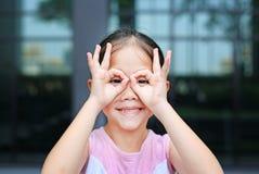 Ευτυχές μικρό κορίτσι με τα γυαλιά χεριών μπροστά από τα μάτια της στοκ φωτογραφία