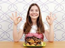 Ευτυχές μικρό κορίτσι με τα croissant και εντάξει σημάδια χεριών στοκ εικόνα