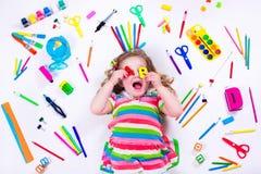 Ευτυχές μικρό κορίτσι με τις σχολικές προμήθειες Στοκ Φωτογραφία