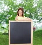 Ευτυχές μικρό κορίτσι με τον κενό πίνακα Στοκ φωτογραφία με δικαίωμα ελεύθερης χρήσης