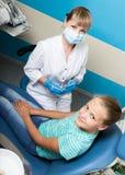 Ευτυχές μικρό κορίτσι με το ανοικτό στόμα που υποβάλλεται στην οδοντική επεξεργασία στην κλινική Οδοντίατρος που ελέγχεται και πο Στοκ εικόνα με δικαίωμα ελεύθερης χρήσης