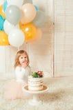 Ευτυχές μικρό κορίτσι με το κέικ γενεθλίων της και ζωηρόχρωμα μπαλόνια στο δωμάτιο Στοκ εικόνες με δικαίωμα ελεύθερης χρήσης