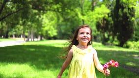 Ευτυχές μικρό κορίτσι με το κίτρινο φόρεμα που τρέχει χωρίς παπούτσια στην πράσινη χλόη στο πάρκο απόθεμα βίντεο