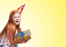 Ευτυχές μικρό κορίτσι με το κιβώτιο δώρων στην κίτρινη ανασκόπηση Στοκ φωτογραφία με δικαίωμα ελεύθερης χρήσης