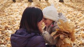 Ευτυχές μικρό κορίτσι που αγκαλιάζει τη μητέρα της στο πάρκο φθινοπώρου απόθεμα βίντεο