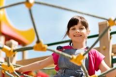 Ευτυχές μικρό κορίτσι που αναρριχείται στην παιδική χαρά παιδιών στοκ εικόνα