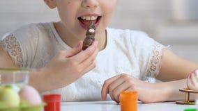 Ευτυχές μικρό κορίτσι που απολαμβάνει το νόστιμο κουνέλι σοκολάτας, γλυκό δώρο Πάσχας, παιδική ηλικία φιλμ μικρού μήκους