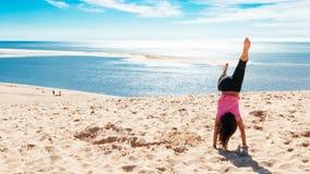 Ευτυχές μικρό κορίτσι που κάνει ένα handstand στην παραλία Στοκ Φωτογραφίες
