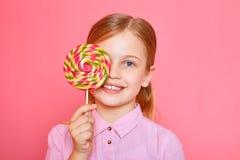 Ευτυχές μικρό κορίτσι που καλύπτει μια καραμέλα ματιών στο ρόδινο υπόβαθρο Στοκ Φωτογραφία