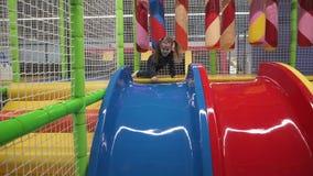 Ευτυχές μικρό κορίτσι που κινείται κάτω από τη φωτογραφική διαφάνεια στην παιδική χαρά στο κέντρο των παιδιών φιλμ μικρού μήκους