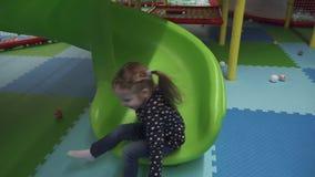 Ευτυχές μικρό κορίτσι που κινείται κάτω στη φωτογραφική διαφάνεια στο κέντρο παιχνιδιού των παιδιών απόθεμα βίντεο