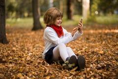 Ευτυχές μικρό κορίτσι που κουβεντιάζει στο smartphone Επικοινωνία, εκπαίδευση, σχολείο, τεχνολογία και έννοια Διαδικτύου στοκ εικόνα