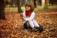 Ευτυχές μικρό κορίτσι που κουβεντιάζει στο smartphone Επικοινωνία, εκπαίδευση, σχολείο, τεχνολογία και έννοια Διαδικτύου στοκ εικόνες