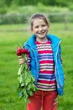Ευτυχές μικρό κορίτσι που κρατά μια δέσμη των ραδικιών Στοκ εικόνα με δικαίωμα ελεύθερης χρήσης