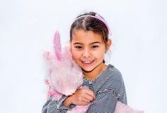 Ευτυχές μικρό κορίτσι που κρατά το ρόδινο παιχνίδι μονοκέρων απομονωμένο στο λευκό Στοκ φωτογραφίες με δικαίωμα ελεύθερης χρήσης