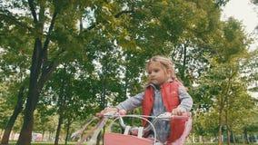 Ευτυχές μικρό κορίτσι που οδηγά ένα ποδήλατο σε υπαίθριο απόθεμα βίντεο