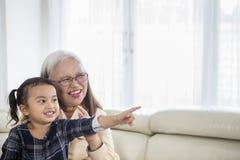 Ευτυχές μικρό κορίτσι που προσέχει τη TV με τη γιαγιά της στοκ εικόνα με δικαίωμα ελεύθερης χρήσης