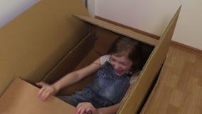 Ευτυχές μικρό κορίτσι που προσπαθεί να βγεί από το κουτί από χαρτόνι απόθεμα βίντεο