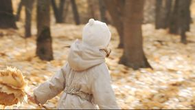 Ευτυχές μικρό κορίτσι που τρέχει με τα φύλλα φθινοπώρου στο πάρκο απόθεμα βίντεο
