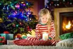 Ευτυχές μικρό κορίτσι που φορά τις πυτζάμες Χριστουγέννων που παίζουν από μια εστία σε ένα άνετο σκοτεινό καθιστικό στη Παραμονή  στοκ εικόνα με δικαίωμα ελεύθερης χρήσης