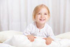 Ευτυχές μικρό κορίτσι σε ένα κρεβάτι Στοκ Εικόνες