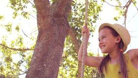 Ευτυχές μικρό κορίτσι σε μια ταλάντευση στο πάρκο απόθεμα βίντεο