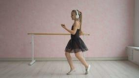 Ευτυχές μικρό κορίτσι στα ακουστικά που ακούει τη μουσική από το smartphone και το χορό απόθεμα βίντεο