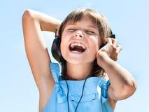 Ευτυχές μικρό κορίτσι στα ακουστικά Στοκ φωτογραφία με δικαίωμα ελεύθερης χρήσης