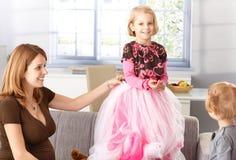Ευτυχές μικρό κορίτσι στη φούστα πριγκηπισσών στο σπίτι Στοκ Φωτογραφία