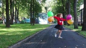Ευτυχές μικρό κορίτσι στις περιστροφές φουστών με τα φωτεινά μπαλόνια απόθεμα βίντεο