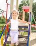 Ευτυχές μικρό κορίτσι στον υπαίθριο εξοπλισμό παιδικών χαρών στοκ εικόνες