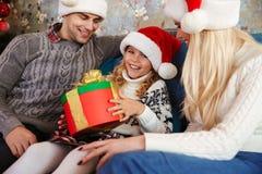 Ευτυχές μικρό κορίτσι στο καπέλο Santa ` s που κρατά παρόν, εξετάζοντας το έκκεντρο Στοκ Εικόνα
