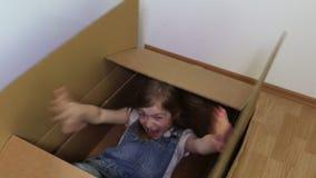 Ευτυχές μικρό κορίτσι στο κουτί από χαρτόνι απόθεμα βίντεο