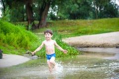 Ευτυχές μικρό παιδί που έχει τη διασκέδαση και που τρέχει στο νερό στον ποταμό στο χρόνο θερινής ημέρας, υπαίθρια, φιλική οικογέν Στοκ φωτογραφία με δικαίωμα ελεύθερης χρήσης