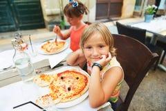 Ευτυχές μικρό παιδί που τρώει την πίτσα παιδιών ` s στο εστιατόριο Στοκ Εικόνες