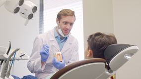 Ευτυχές μικρό παιδί που χαμογελά στη κάμερα κατά τη διάρκεια του ιατρικού appointement με τον οδοντίατρο απόθεμα βίντεο