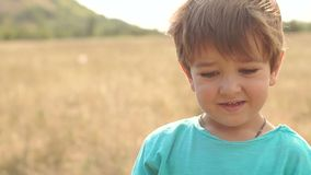 Ευτυχές μικρό παιδί προσώπου κινηματογραφήσεων σε πρώτο πλάνο σε έναν τομέα στο ηλιοβασίλεμα απόθεμα βίντεο
